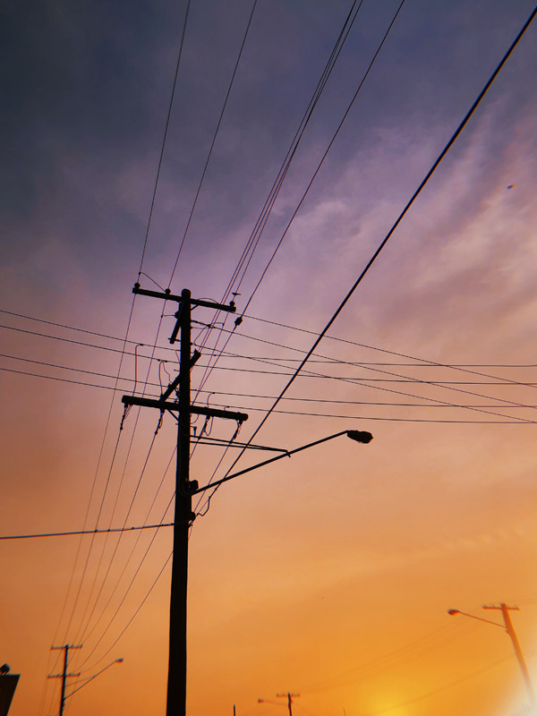 a photo of the sky at sunset. the sky is very dark blue at the top, fading to purple in the middle and yellow at the bottom. in the foreground is a power pole, silhouetted against the sky